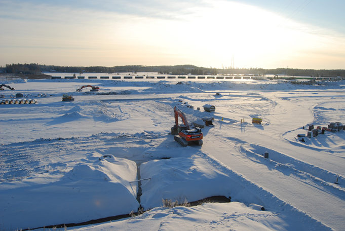 Lumisella työmaalla kaivinkoneet ja taustalla raiteilla kulkeva tavarajuna.