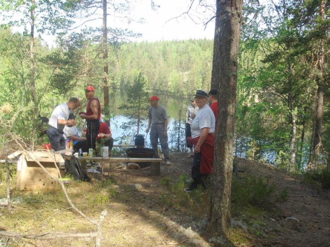 Kuvassa retkeilijöitä nuotiopaikalla metsässä korkealla mäen päällä. Taustalla järvi ja metsää. Aurinko paistaa.