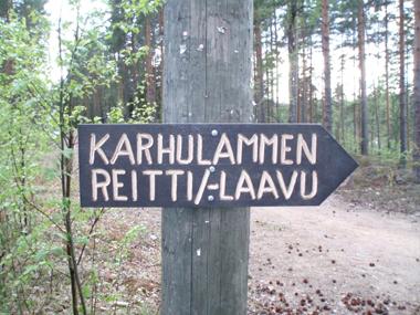 Kuvassa pylvääseen kiinnitetty kyltti, jossa teksti Karhulammen reitti/-laavu