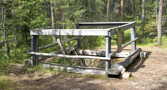 Kuvassa puinen turva-aita hiidenkirnun ympärillä.