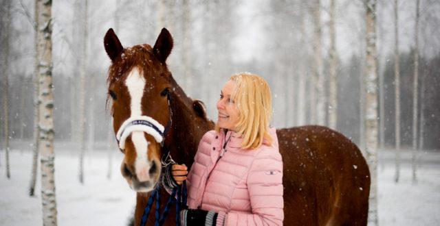 Päivi Kähkönen lumisateessa hevonsensa kanssa