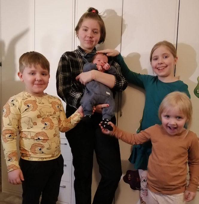 Vauva isosiskon sylissä, ympärillä kolme muuta sisarusta, poika ja kaksi tyttöä. Iloiset ilmeet,