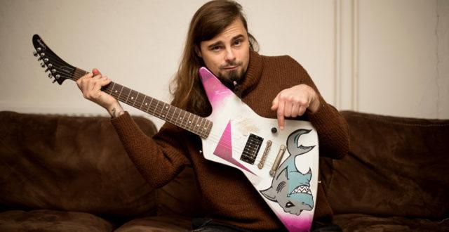Tarmo Ranta sohvalla kitaran kanssa