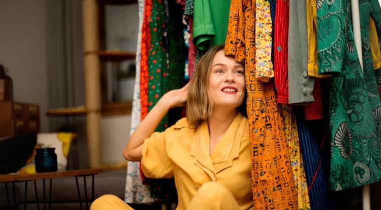 Tiina Winter keltaisessa haalarissa kotonaan värikkäiden vaatteiden keskellä