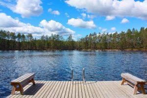 Kuvassa järvi ja etualalla laituri, jolla kaksi penkkiä ja portaat järveen. Järven toisella rannalla metsää. Taivas on kirkas ja puolipilvinen.