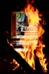Lähikuvassa tulet grillikodan tulisijassa. Taustalla kodan oviaukosta tulee valoa sisään.