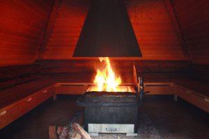 Kuvassa grillikodan sisällä tulet tulisijassa. Tuli heijastaa kotaan punaisen sävyn.