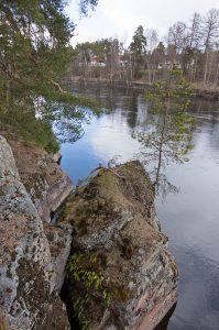 Kuvassa kallionreunaa, irtolohkare ja puita. Alhaalla näkyy sininen tyyni joen pinta.