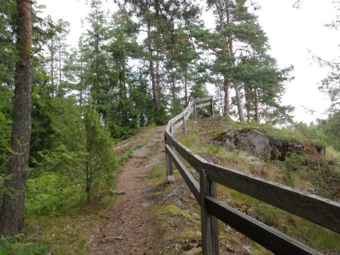 Kuvassa polku kulkee kallion päälle. Polun oikealla puolella kulkee puinen turva-aita.