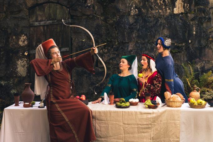 Kolme naista istuu pöydän ääressä ja hämmästelee neljättä , pöydällä istuvaa naista, joka on virittänyt jousipyssyn yläviistoon. Pöydällä hedelmiä. Naisilla vanhat mutta värikkäät vaatteet ja päähineet.
