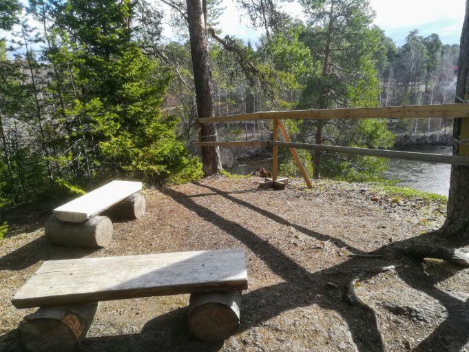 Kuvassa lankuista tehdyt kaksi penkkiä korkealla kallion päällä. Kahden puun välissä on puinen turva-aita. Alhaalla näkyy virtaava joki.