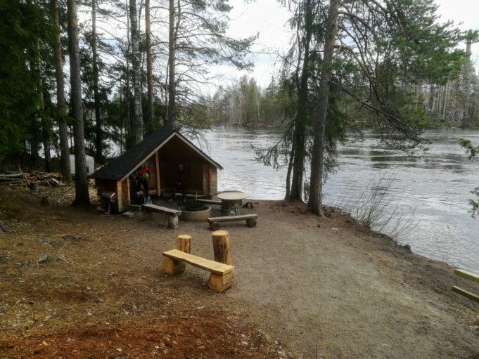 Kuvassa kota ja nuotiopaikka virtaavan joen rannalla.