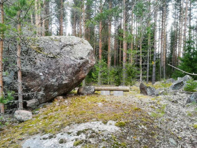 Kuvassa suuri kivenlohkare kallion päällä. Taustalla mäntymetsää.
