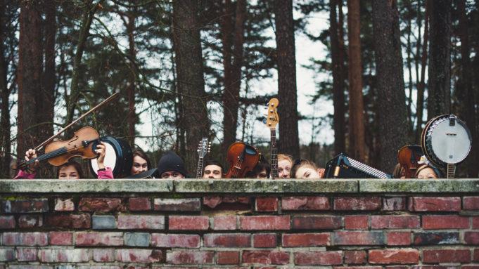 Hauska kuva Takapotku bändiläisistä. Kurkistavat tiilimuurin takaa, josta näkyy kasvoja ja ilmaan nostettuja soittimia.