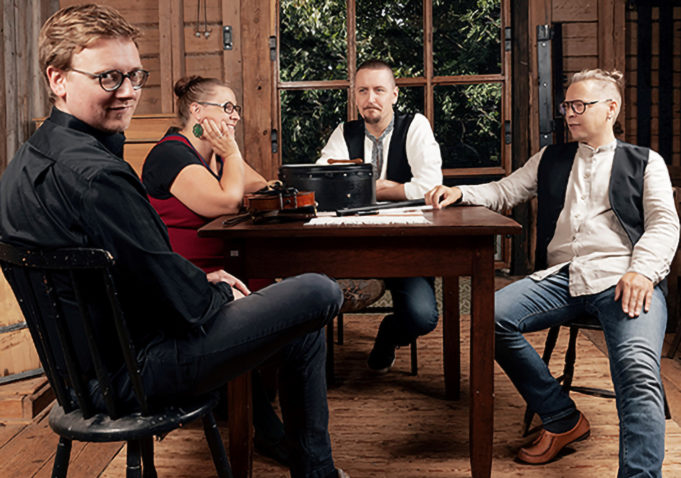 Lebrechauns bändi istuu suuren pöydän ympärillä. Bändi soittaa irkkumusiikkia.