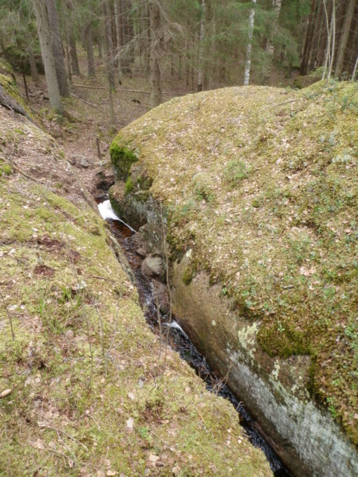 Kuvassa sammalpeitteisten kallionlohkareiden välissä kulkee puro. Taustalla kuusimetsää.