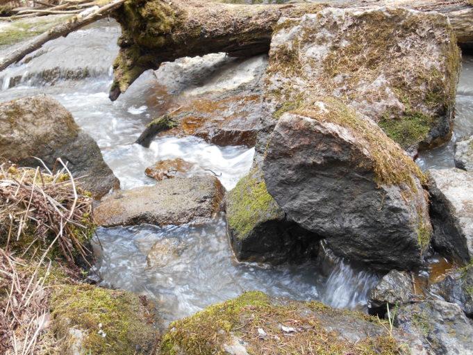 Kuvassa kivenlohkareita ja niiden välissä virtaa vettä.