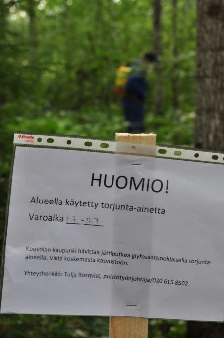 Kuvassa kyltti maastossa, jossa varoitusteksti, että alueella on käytetty torjunta-ainetta.
