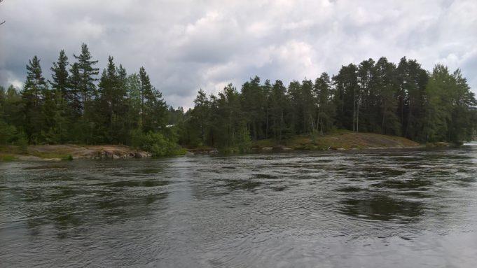 Kuvassa virtaava joen pinta. Vastarannalla kalliota ja metsää. Taivas on pilvinen.
