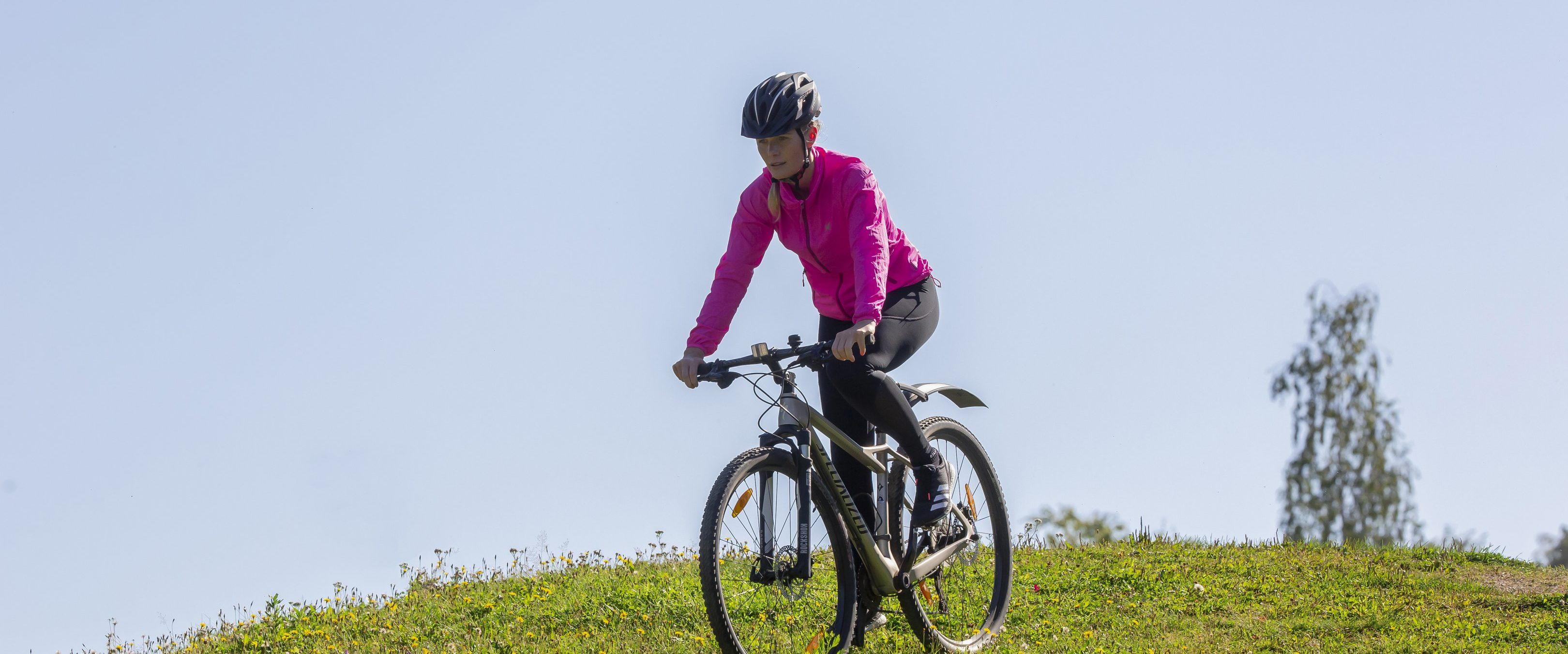 Nainen pyöräilee puistossa.