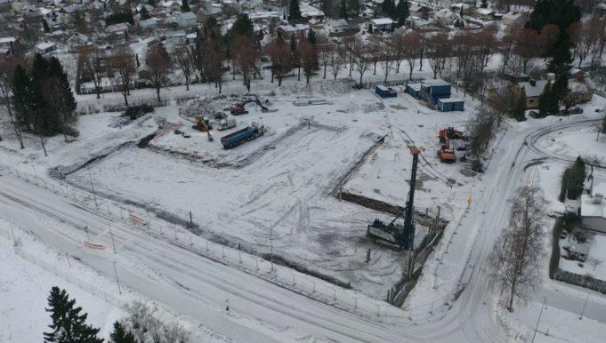 Ilmakuva Sarkolan koulun työmaalta. Luminen maisema, työkoneita työmaalla.