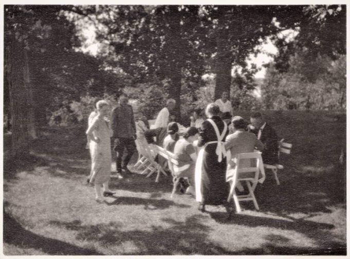 Vanha mustavalkoinen kuva puutarhassa kahvittelevista ihmisistä ja naisesta jolla on essu päällä.