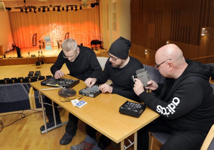 Kuvassa Harri Peltola istuu oikealla, keskellä Matti Kalevi Pasi ja vasemmalla Antti Salminen.