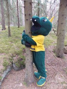 Liikuntamaskotti Kääkki halaa puuta.
