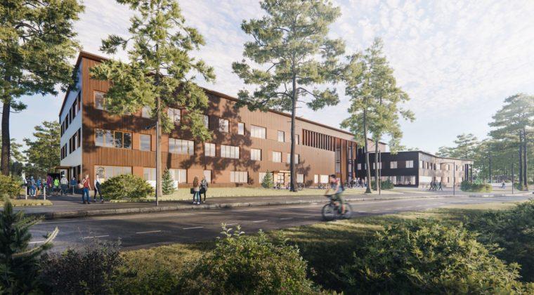 Arkkitehtitoimiston havainnekuva puupintaisesta isosta koulurakennuksesta, jonka edustalla kulkee tie ja kasvaa mäntyjä. Oppilaita näkyy piha-alueella.