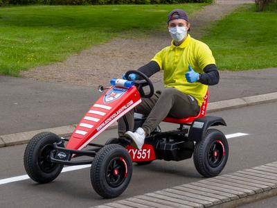 Mies keltaisessa paidassa ja maski naamalla ajaa uutta punaista Kouvolan VPK:n lahjoittamaa polkuautoa ja näyttää peukkua.