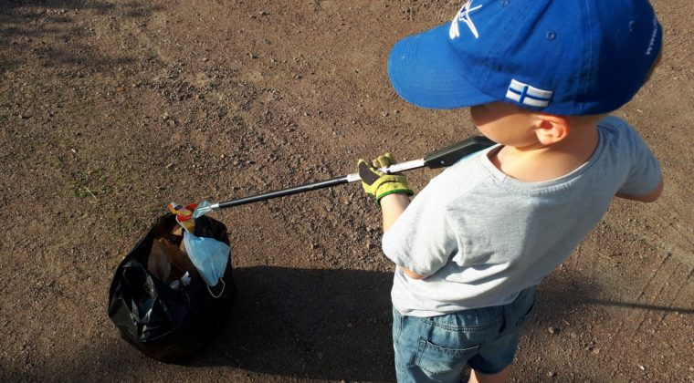 Poika laittaa roskpihdeillä roskia roskapussiin