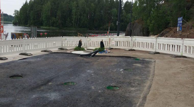 Polttoainejakelua varten tehty asfalttikenttä Virtakiven satamassa on rajattu valkoisilla työmaa-aidoilla. Taustalla näkyy Pyhäjärvi.