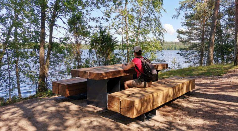 Nainen istuu reppu selässä jykevän puupöydän ääressä ja katsoo järvelle.