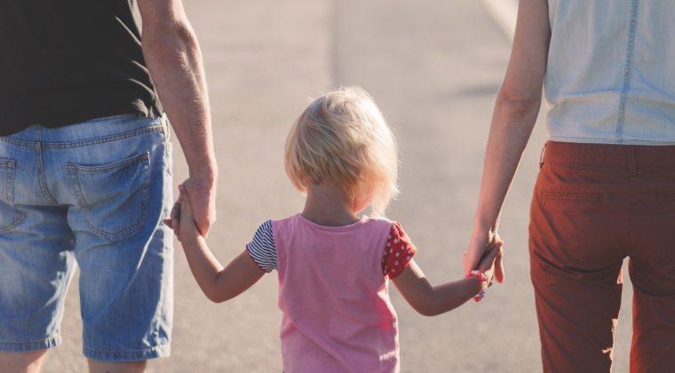 kaksi aikuista kävelee tiellä pitäen lasta kädestä.