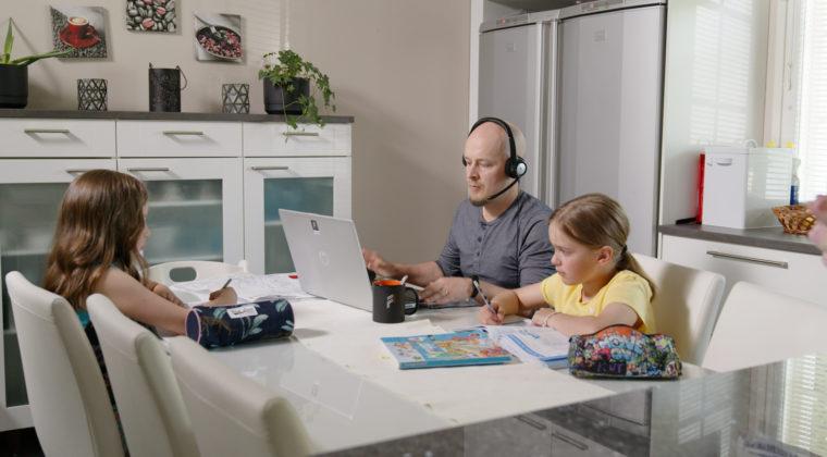 Lapset tekevät läksyjä pöydän ääressä ja isä tekee samalla töitä tietokoneella.