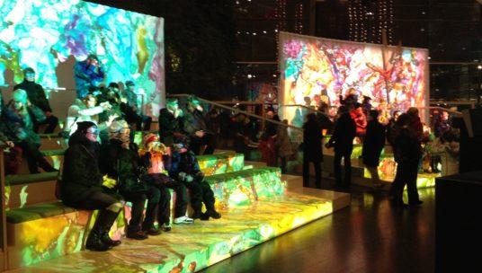 Ihmiset istumassa katsomossa katsomassa katsomassa valotaideteosta.