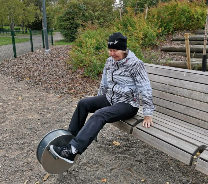 Nainen istuu puiston penkillä ja polkee maassa olevaa seniorikuntoilulaitetta.