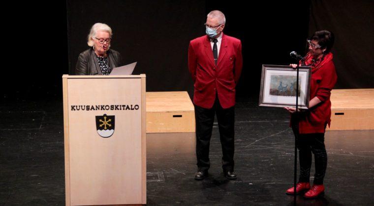 Nainen puhujapöntössä lukee puhetta. Vieressä mies punaisessa takissa sekä nainen taulu kädessä.