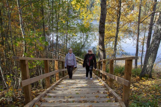 Kaksi naista kävelemässä rappuja ylös Kymijoen ulkoilureitillä. Puissa keltaisia lehtiä. Taustalla näkyy Kymijoki.