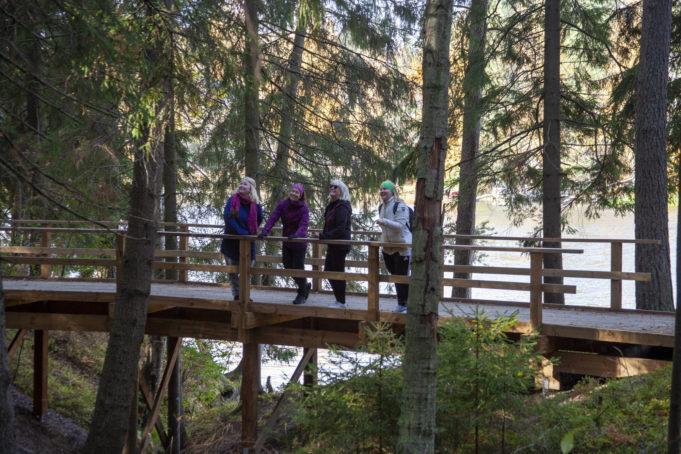 Neljä naista Kymijoen ulkoilureitille rakennetulla kävelysillalla. Taustalla näkyy Kymijoki-